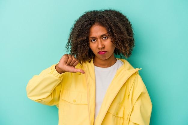 Giovane donna afroamericana con capelli ricci isolati su fondo blu che mostra pollice giù, concetto di delusione.