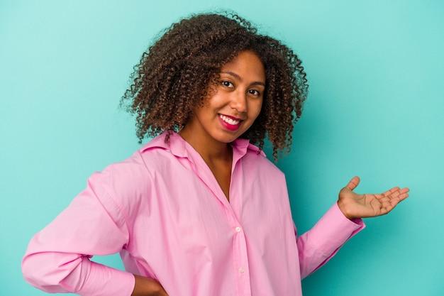 Giovane donna afroamericana con capelli ricci isolati su fondo blu che mostra un'espressione benvenuta.