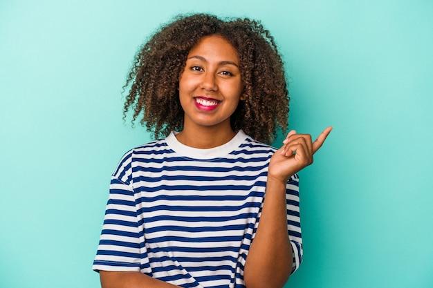 Giovane donna afroamericana con capelli ricci isolati su fondo blu che sorride allegramente indicando con l'indice via.