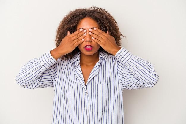 Giovane donna afroamericana con capelli ricci isolati su fondo bianco impaurito che copre gli occhi con le mani.