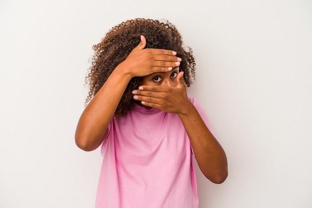 La giovane donna afroamericana con capelli ricci isolati su fondo bianco sbatte le palpebre alla macchina fotografica tramite le dita, fronte che copre imbarazzato.