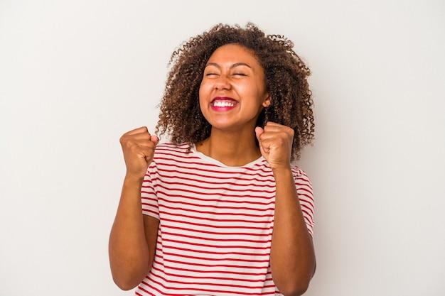 Giovane donna afroamericana con capelli ricci isolati su fondo bianco che celebra una vittoria, passione ed entusiasmo, espressione felice.
