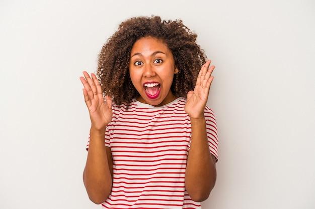 Giovane donna afroamericana con capelli ricci isolato su sfondo bianco che celebra una vittoria o un successo, è sorpreso e scioccato.