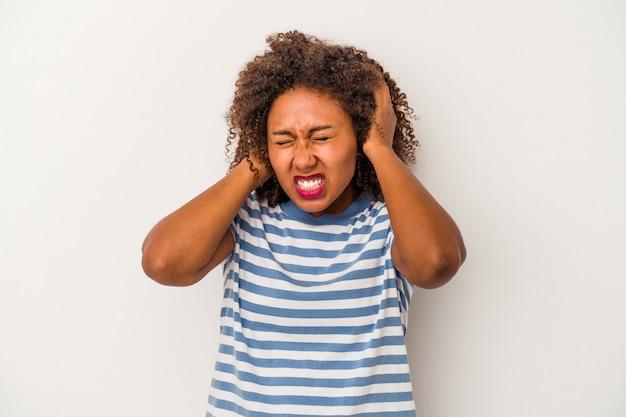 Giovane donna afroamericana con capelli ricci isolati su fondo bianco che copre le orecchie con le mani.