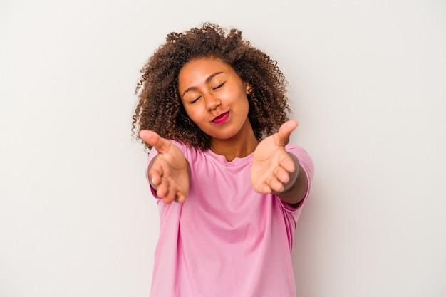 Giovane donna afroamericana con capelli ricci isolati su fondo bianco piegando le labbra e tenendo le palme per inviare un bacio d'aria.