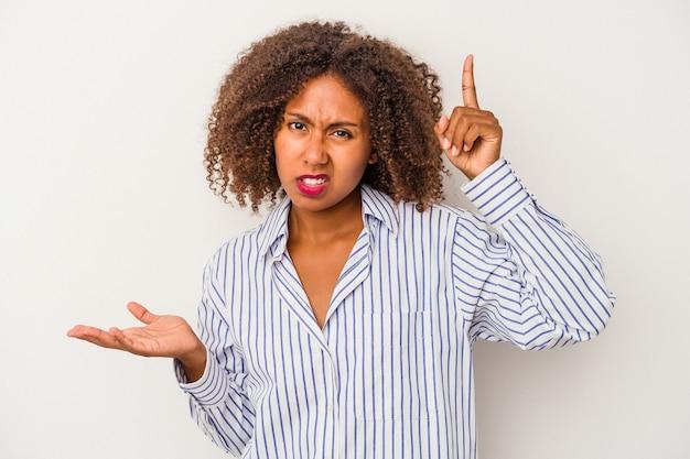 Giovane donna afroamericana con capelli ricci isolati su fondo bianco che tiene e che mostra un prodotto a disposizione.