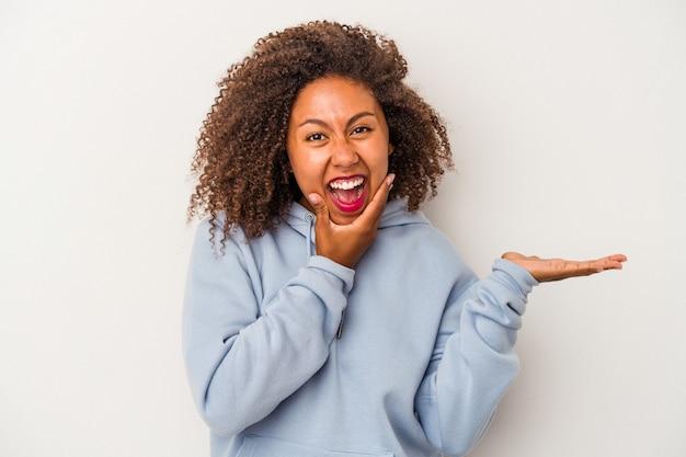 La giovane donna afroamericana con capelli ricci isolati su fondo bianco tiene lo spazio della copia su una palma, tiene la mano sulla guancia. stupito e deliziato.