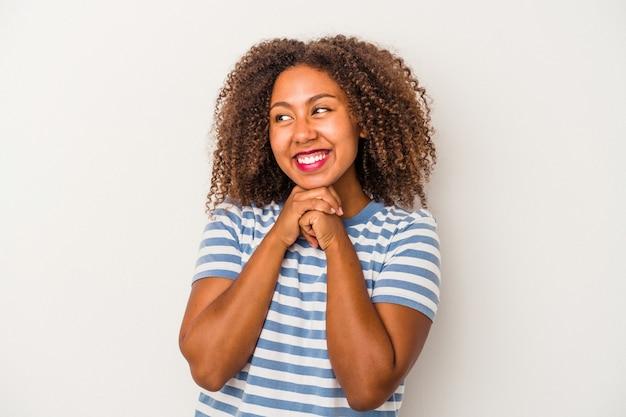 La giovane donna afroamericana con capelli ricci isolati su fondo bianco tiene le mani sotto il mento, sta guardando felicemente da parte.