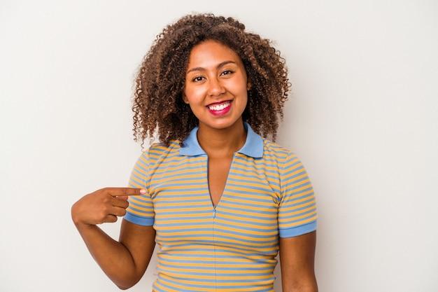 Giovane donna afroamericana con capelli ricci isolata sulla persona bianca del fondo che indica a mano uno spazio della copia della camicia, orgoglioso e sicuro