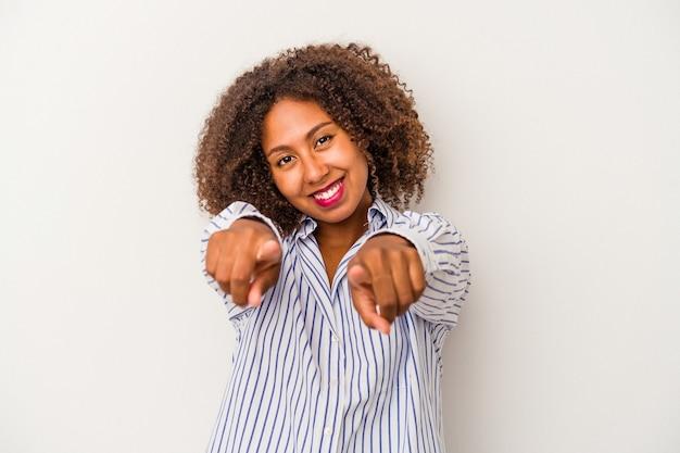 Giovane donna afroamericana con capelli ricci isolati su fondo bianco che indica la parte anteriore con le dita.
