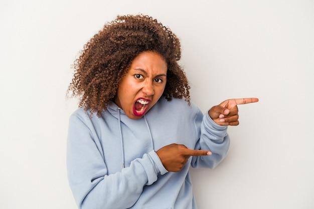 Giovane donna afroamericana con i capelli ricci isolato su sfondo bianco che indica con l'indice uno spazio di copia, esprimendo eccitazione e desiderio.