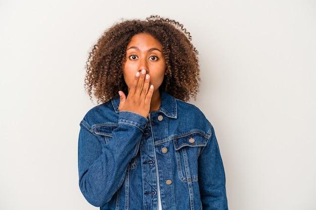 Giovane donna afroamericana con i capelli ricci isolati su sfondo bianco scioccata, coprendosi la bocca con le mani, ansiosa di scoprire qualcosa di nuovo.