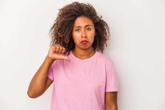 Giovane donna afroamericana con capelli ricci isolati su fondo bianco che mostra un gesto di antipatia, pollice verso. concetto di disaccordo.