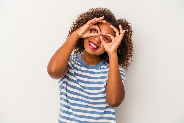 La giovane donna afroamericana con capelli ricci isolati su fondo bianco che mostra bene firma sopra gli occhi
