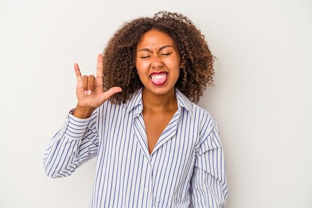 Giovane donna afroamericana con capelli ricci isolati su fondo bianco che mostra gesto rock con le dita