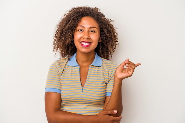 Giovane donna afroamericana con capelli ricci isolati su fondo bianco che sorride allegramente indicando con l'indice via.