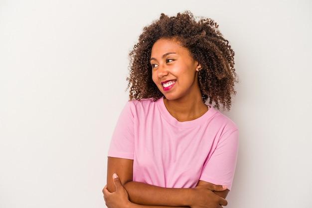 Giovane donna afroamericana con capelli ricci isolati su fondo bianco sorridente fiducioso con le braccia incrociate.