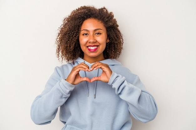 La giovane donna afroamericana con capelli ricci ha isolato su fondo bianco che sorride e che mostra una forma del cuore con le mani.