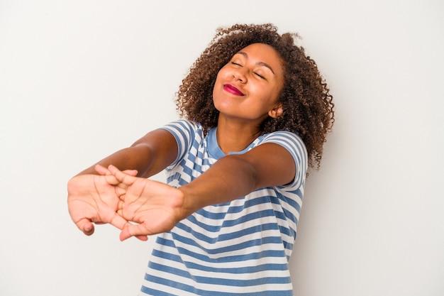 Giovane donna afroamericana con capelli ricci isolati su fondo bianco che allunga le braccia, posizione rilassata.