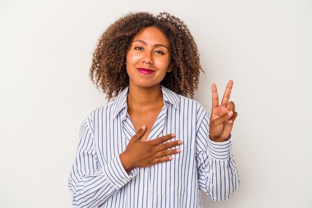 Giovane donna afroamericana con capelli ricci isolati su fondo bianco che presta giuramento, mettendo la mano sul petto.
