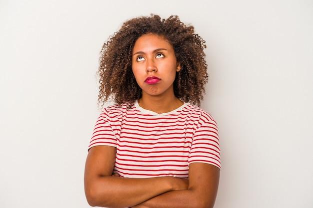 Giovane donna afroamericana con i capelli ricci isolato su sfondo bianco stanco di un compito ripetitivo.