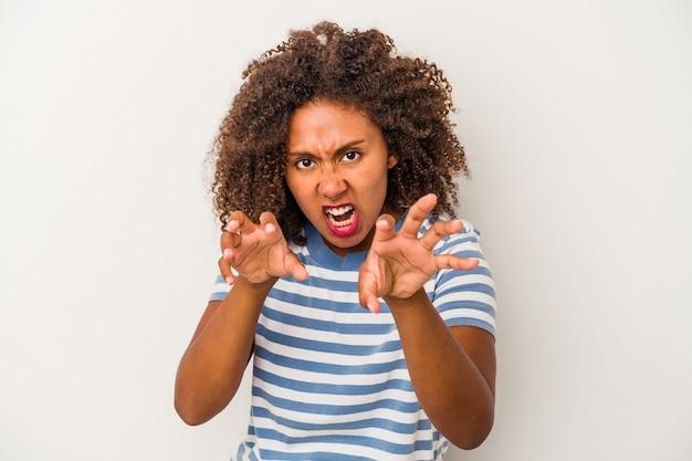 Giovane donna afroamericana con capelli ricci isolati su priorità bassa bianca sconvolta urlando con le mani tese.