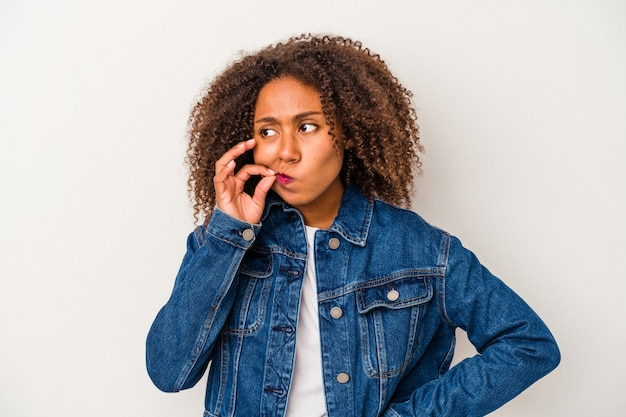 Giovane donna afroamericana con capelli ricci isolati su fondo bianco con le dita sulle labbra che tengono un segreto.