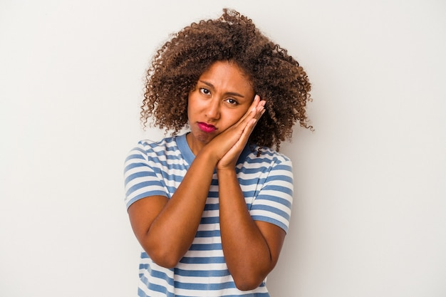 Giovane donna afroamericana con capelli ricci isolati su fondo bianco che sbadiglia mostrando un gesto stanco che copre la bocca con la mano.