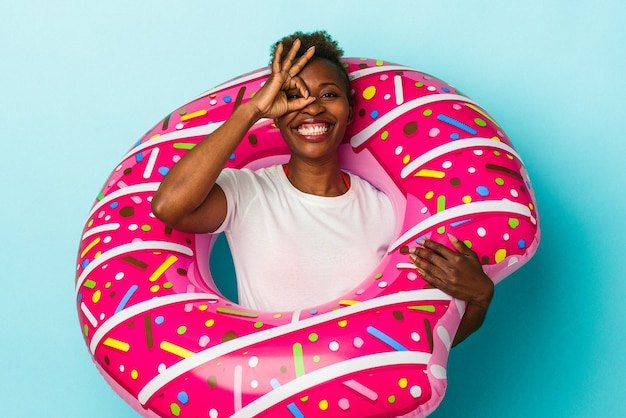 La giovane donna afroamericana con la ciambella gonfiabile isolata su fondo blu ha eccitato mantenendo il gesto giusto sull'occhio.