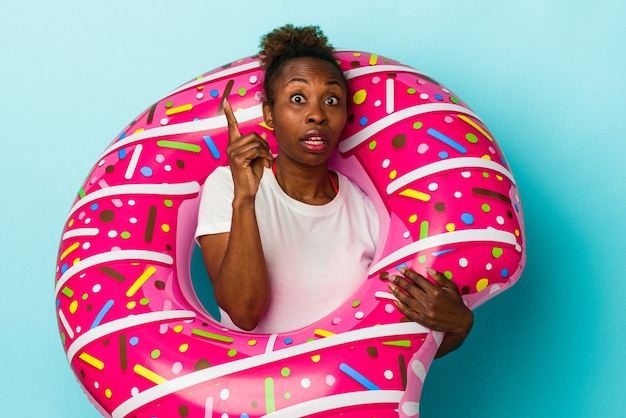 Giovane donna afroamericana con ciambella gonfiabile isolata su fondo blu che ha un'idea, concetto di ispirazione.