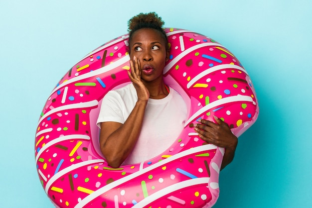 La giovane donna afroamericana con la ciambella gonfiabile isolata su fondo blu sta dicendo una notizia segreta di frenata calda e sta guardando da parte