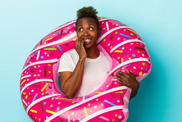 La giovane donna afroamericana con la ciambella gonfiabile isolata su fondo blu si è rilassata pensando a qualcosa che esamina uno spazio della copia.