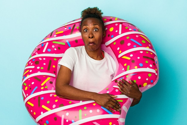 La giovane donna afroamericana con la ciambella gonfiabile isolata su fondo blu alza le spalle e apre gli occhi confusi.