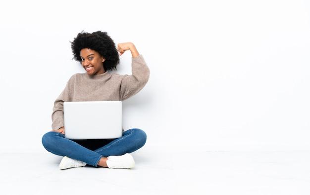 Giovane donna afroamericana con un computer portatile che si siede sul pavimento che fa forte gesto