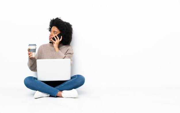 Giovane donna afroamericana con un computer portatile che si siede sul pavimento che tiene caffè da portare via e un cellulare