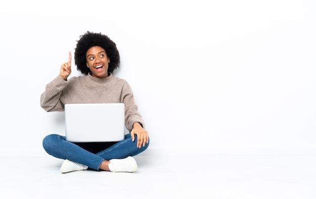 Giovane donna afroamericana con un laptop seduto sul pavimento che intende realizzare la soluzione mentre alza un dito