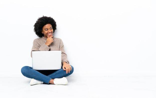 Giovane donna afroamericana con un computer portatile che si siede sul pavimento che osserva al lato