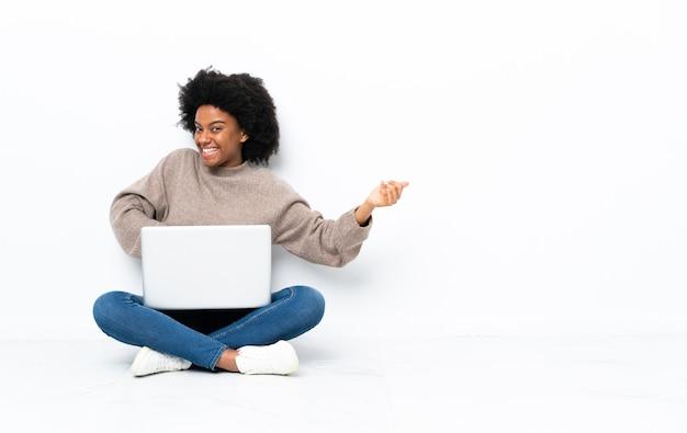 Giovane donna afroamericana con un computer portatile che si siede sul pavimento che fa il gesto della chitarra