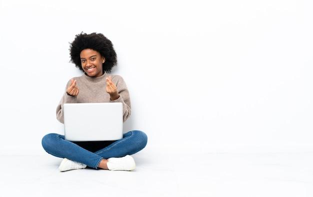 Giovane donna afroamericana con un computer portatile che si siede sul pavimento che fa gesto di soldi