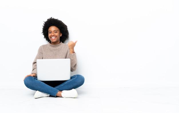 Giovane donna afroamericana con un computer portatile seduto sul pavimento che punta di lato per presentare un prodotto