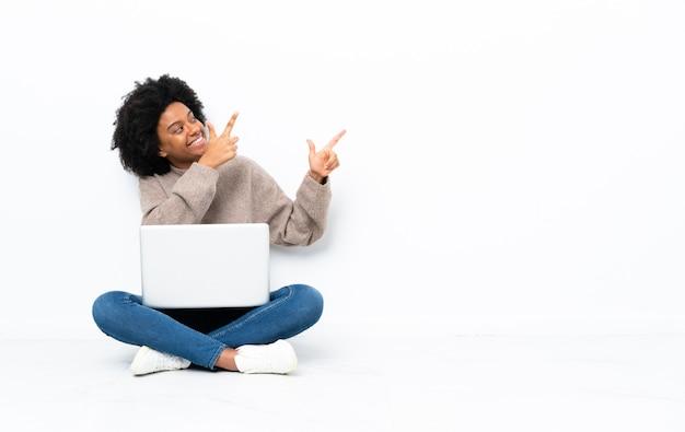 Giovane donna afroamericana con un laptop seduto sul pavimento che punta con il dito indice una grande idea