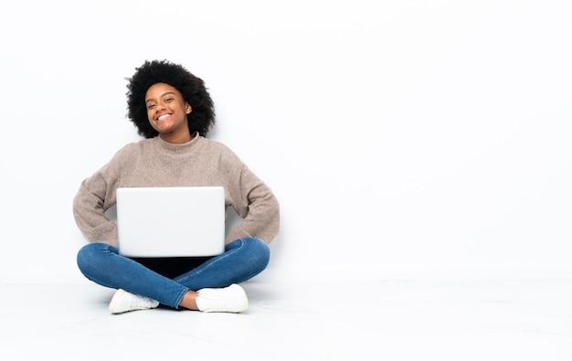 Giovane donna afroamericana con un laptop seduto sul pavimento in posa con le braccia al fianco e sorridente
