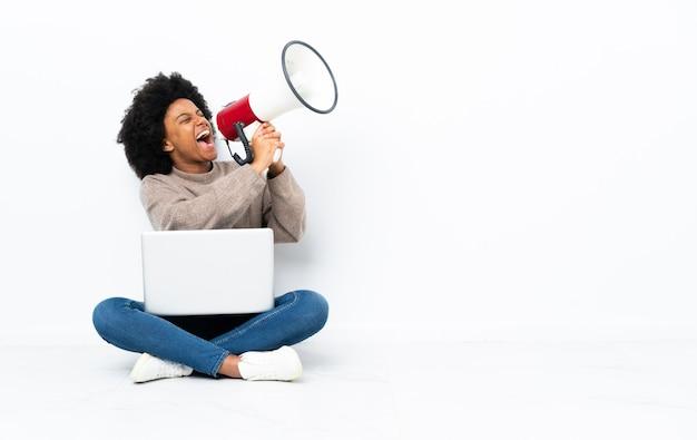 Giovane donna afroamericana con un computer portatile che si siede sul pavimento che grida tramite un megafono