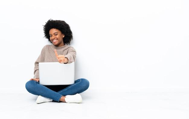 Giovane donna afroamericana con un computer portatile che si siede sul pavimento che mostra e che alza un dito