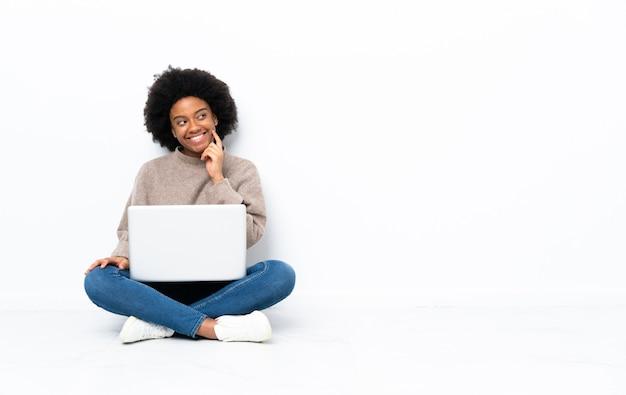 Giovane donna afroamericana con un computer portatile che si siede sul pavimento che pensa un'idea mentre osserva in su