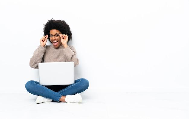 Giovane donna afroamericana con un laptop seduto sul pavimento con gli occhiali e sorpreso