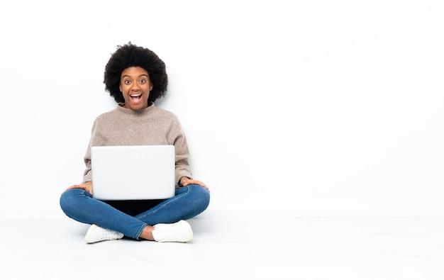 Giovane donna afro-americana con un computer portatile seduto sul pavimento con espressione facciale sorpresa