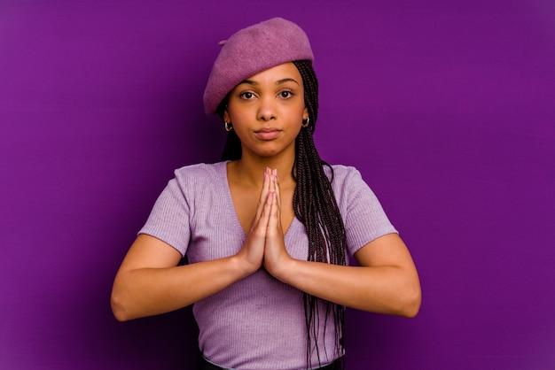 Giovane donna afroamericana giovane donna afroamericana che prega, mostrando devozione, persona religiosa in cerca di ispirazione divina.
