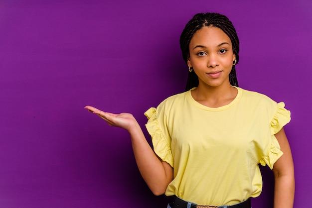 Giovane donna afroamericana giovane donna afroamericana che mostra qualcosa su un palmo e tenendo un'altra mano sulla vita.