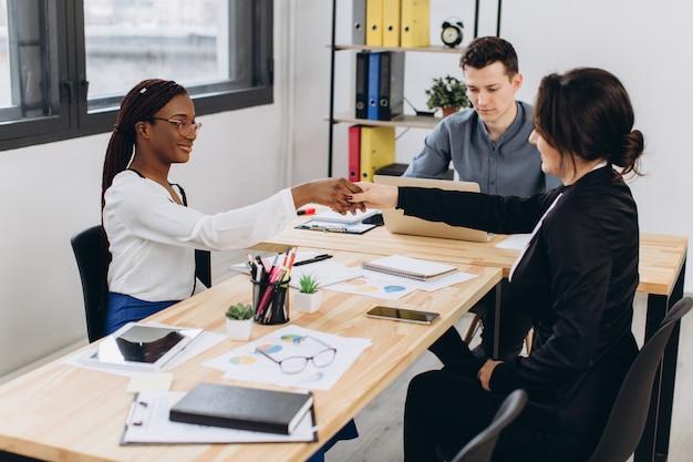 Giovane bella donna africana che ha un'intervista o una riunione d'affari con i datori di lavoro nell'interiore moderno dell'ufficio